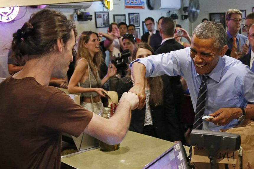 U.S. President Barack Obama fist bumps the cashier after paying for his order at Franklin Barbecue in Austin, Texas. -- PHOTO: REUTERS