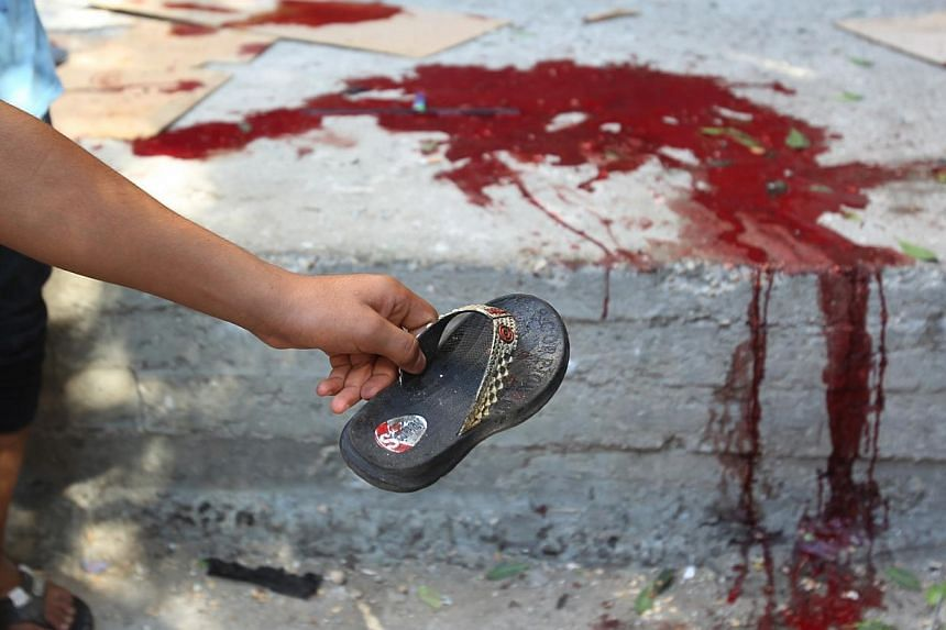 A Palestinian man shows the slipper of a chid as blood is seen on the ground at the scene of an explosion at a public garden in Gaza City on July 28, 2014.Bloodshed in and around Gaza surged on Monday with a strike killing eight Palestinian chi