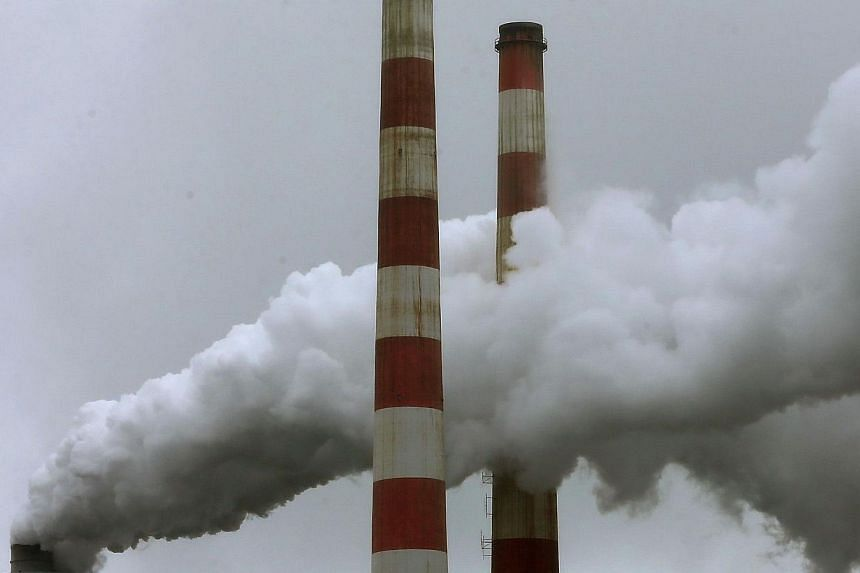 Emissions spew out of a large stack at the coal fired Morgantown Generating Station, on May 29, 2014 in Newburg, Maryland.Delaying efforts to reduce greenhouse gas emissions could cost the US $150 billion (S$190 billion) per year, the White Hou