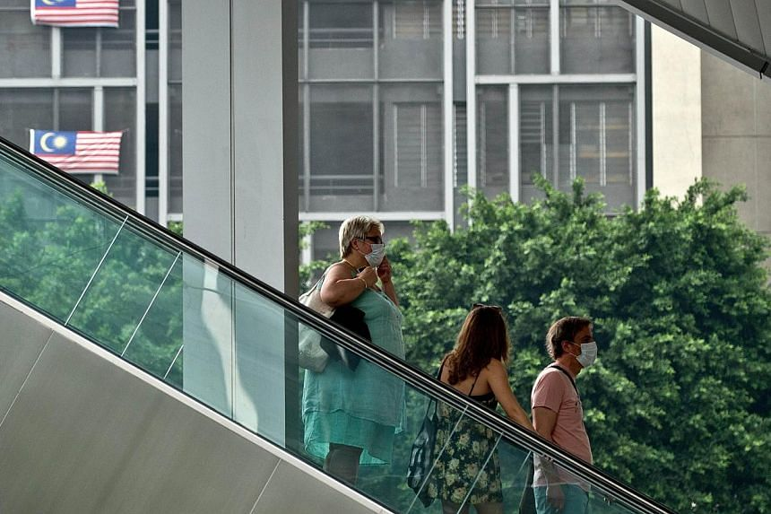 """Foreign tourists wear face masks as they ride an escalator in central Kuala Lumpur on July 29, 2014. Air quality around Malaysia's capital and on Borneo island was """"unhealthy"""", with one town reaching """"very unhealthy"""" levels as haze, mostly from fores"""