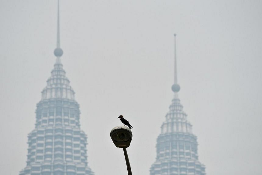 """Malaysia's iconic Twin Towers emerge out of thick haze in Kuala Lumpur on July 29, 2014. Air quality around Malaysia's capital and on Borneo island was """"unhealthy"""", with one town reaching """"very unhealthy"""" levels as haze, mostly from forest fires in I"""