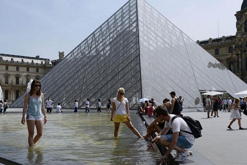 People take in the sun near a fountain in front of the Louvre Pyramid in Paris on July 18, 2014. -- PHOTO: AFP