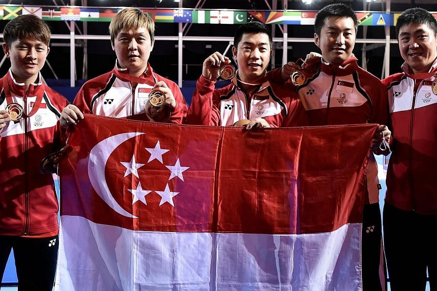 Singapore's players pose with their national flag after winning the gold medal in the table tennis team final at the Scotstoun Sports Campus at the 2014 Commonwealth Games in Glasgow on July 28, 2014.Singapore have won gold in the Commonwealth
