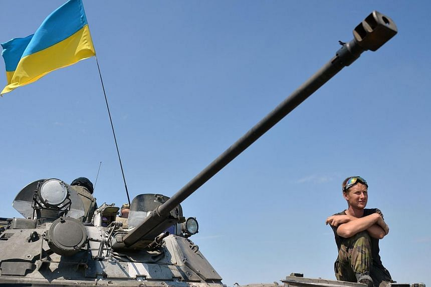 A Ukrainian service man looks out from a tank flying the Ukrainian flag,, part of a convoy of vehicles of the Ukrainian forces driving towards the eastern Ukrainian city of Lysychansk, in the region of Lugansk, on July 25, 2014. Senior American