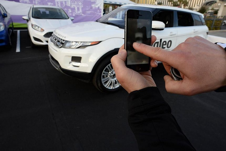 A file photo taken on January 8, 2014 shows a Valeo representative swiping his finger across an iPhone to initiate a self-parking demonstration during a driverless car demo at the 2014 International CES in Las Vegas, Nevada. Driverless cars will