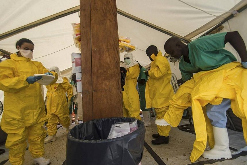"""Medical staff working with Medecins sans Frontieres (MSF) put on their protective gear before entering an isolation area at the MSF Ebola treatment centre in Kailahun on July 20, 2014.The Ebola outbreak in west Africa poses a """"very serious thre"""