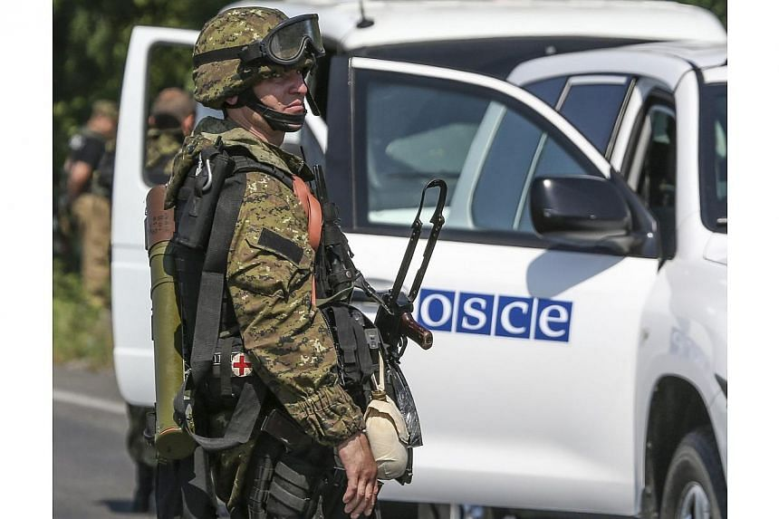 An armed pro-Russian separatist looks back next to a vehicle of the Organisation for Security and Cooperation in Europe's (OSCE) monitoring mission in Ukraine, on the way to the site in eastern Ukraine where the downed Malaysia Airlines flight MH17 c