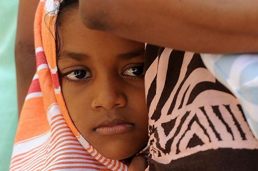 A child among a group of Sri Lankan asylum seekers sent back by Australia looks on before entering the magistrate's court in the southern port district of Galle on July 8, 2014.-- PHOTO: AFP