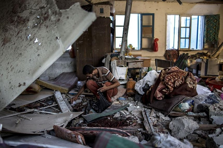 A Palestinian scout collects human remains from a classroom inside a UN school in Gaza City after the area was hit by shelling on July 30, 2014. -- PHOTO: AFP