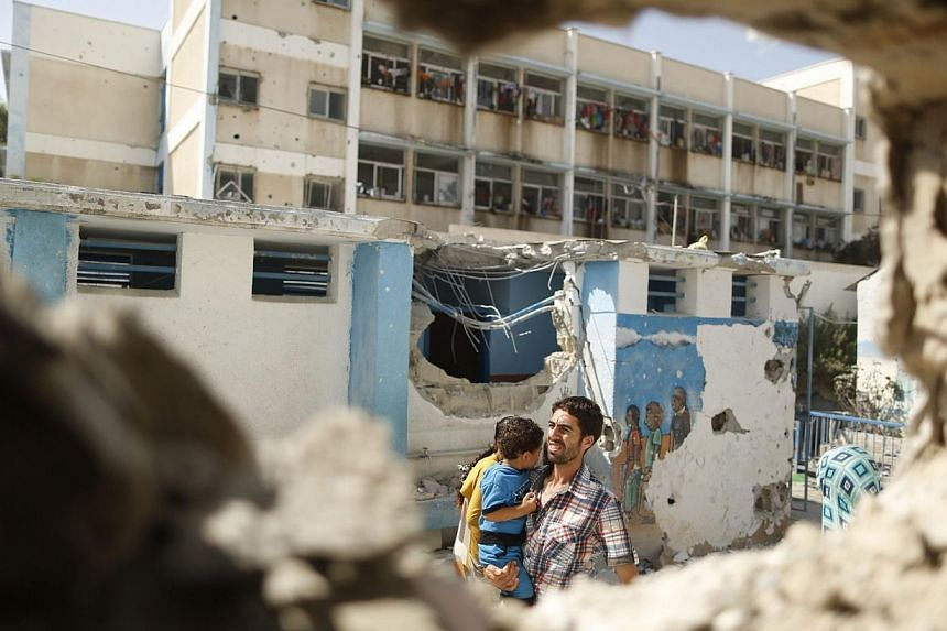 A Palestinian man pictured through a damaged classroom carries a boy as he walks at a United Nations-run school sheltering Palestinians displaced by an Israeli ground offensive, that witnesses said was hit by Israeli shelling, in Jebalya refugee camp