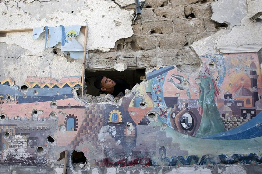 A Palestinian man inspects the damage at a UN school at the Jabalia refugee camp in the northern Gaza Strip after the area was hit by Israeli shelling on July 30, 2014. -- PHOTO: AFP