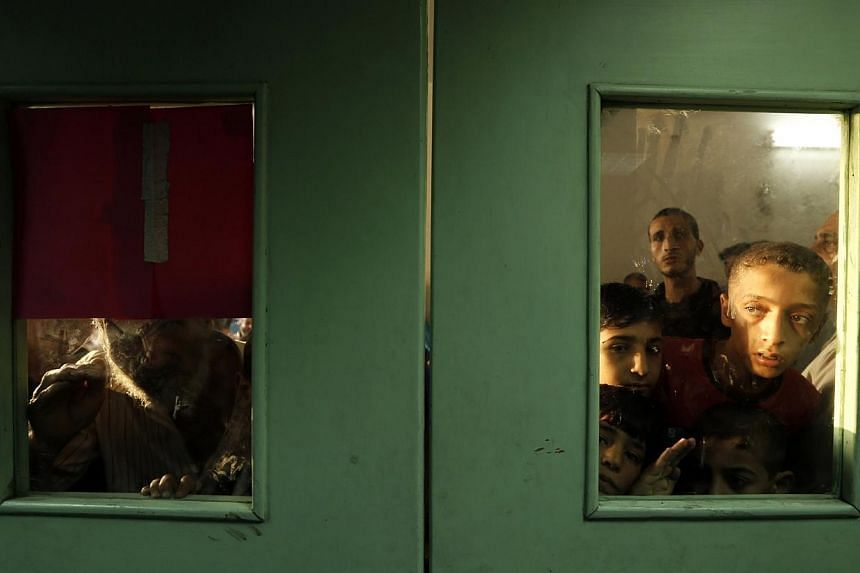 Palestinians look out from behind the doors at Kamal Edwan hospital where victims have been brought following an Israeli strike on a compound housing a UN school in Jabalia refugee camp in the northern Gaza Strip early on July 30, 2014. -- PHOTO: AFP