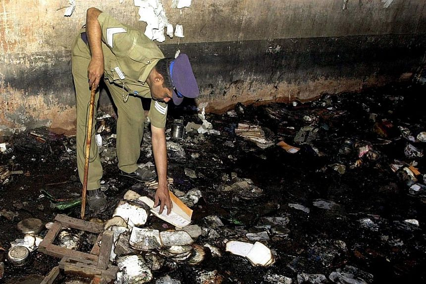 An Indian police officer picks through debris after a fire in a school building in the town of Kumbokonam some 350kms southwest of Chennai on July 16, 2004. -- PHOTO: AFP
