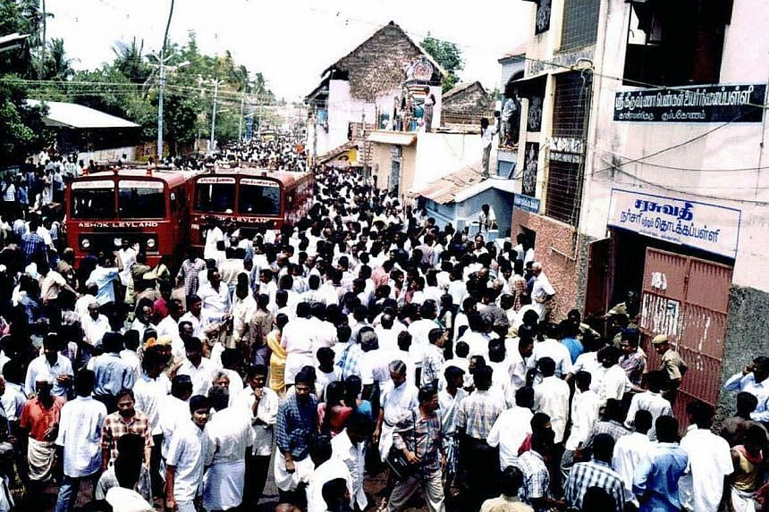 Indian bystanders look on as fire engines arrive at the scene of a fire at a primary school in Kumbakonam, some 350kms south of Chennai on July 16, 2004. -- PHOTO: AFP