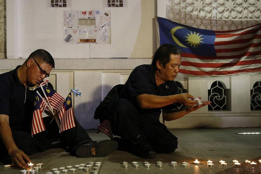 Men light candles at a vigil for victims of Malaysia Airlines Flight MH17 in Kuala Lumpur on July 22, 2014.Families of passengers and crew of the missing Malaysia Airlines (MAS) flight MH370 have offered their help to counsel to the families of