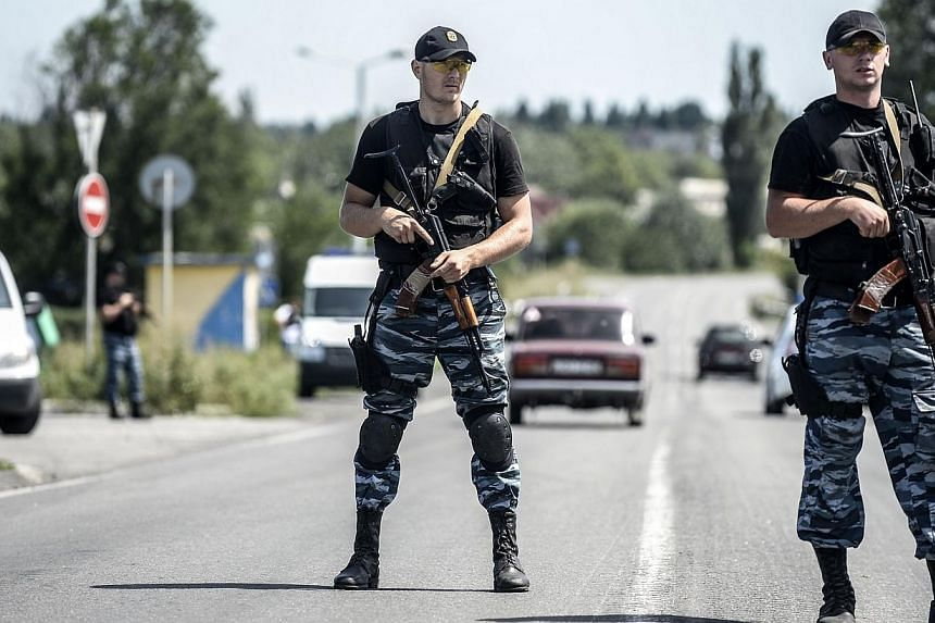 Pro-Russian militants block the road to the crash site of the Malaysia Airlines flight MH17 on July 28, 2014 in Donetsk.Ukraine's army said on Wednesday, July 30, 2014, that it had retaken a town on the outskirts of the main rebel stronghold of