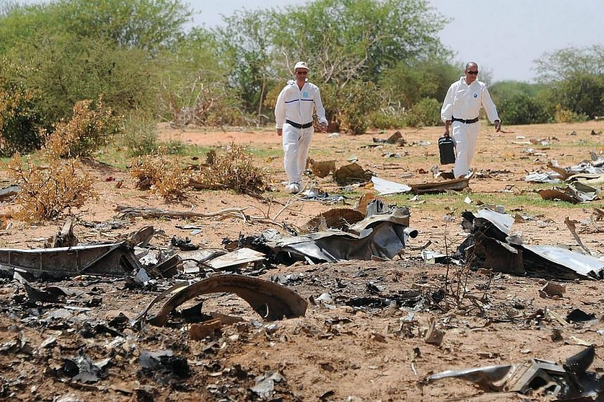 Investigators gather evidence at the crash site of the Air Algerie AH5017 in Mali's Gossi region on July 29, 2014.Dressed in protective white overalls, French experts sift through the debris of the Air Algerie plane that disintegrated ove