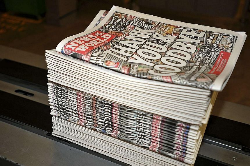 Copies of the final edition of the News of the World roll are seen at the News International print works in Waltham Cross, southern England on July 9, 2011. Two more senior journalists from Rupert Murdoch's defunct British tabloid the News of th