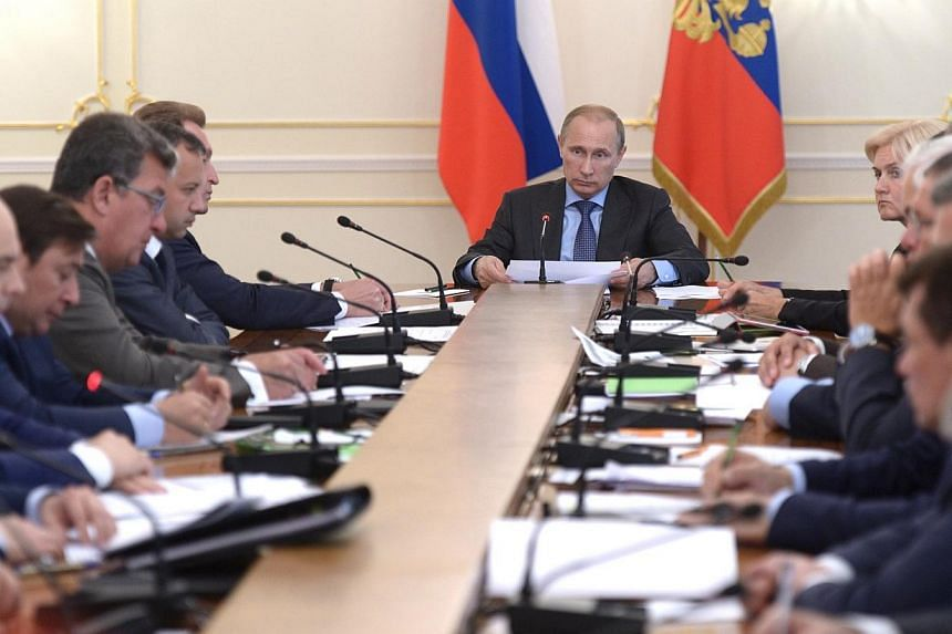 Russia's President Vladimir Putin (centre) chairs a government meeting at the Novo-Ogaryovo state residence outside Moscow on July 30, 2014.Russia fought back on Wednesday, July 30, 2014, over new United States and European Union sanctions impo