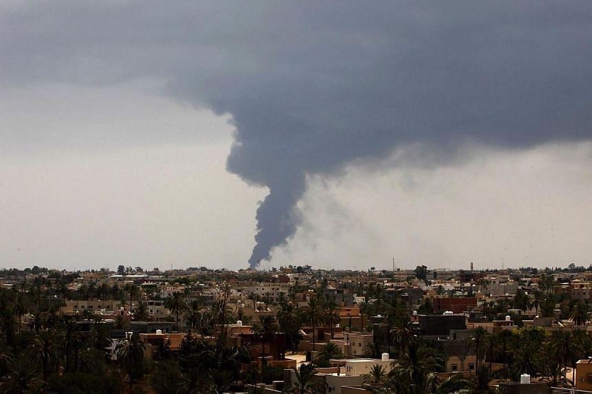 Plumes of smoke rise in the sky after a rocket hit a fuel storage tank near the airport road in Tripoli, during clashes between rival militias on July 28, 2014. -- PHOTO: REUTERS