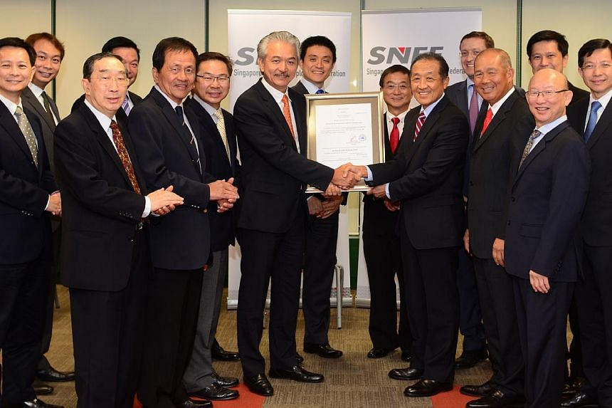 Mr Stephen Lee (centre, right) handing over the Certificate of Registration of SNEF to Dr Robert Yap (centre, left) at the SNEF Council Meeting on July 30, 2014. From left to right: Dr Lim Suet Wun, Mr Douglas Foo, Mr Freddy Lam (front), Mr Robert Ya