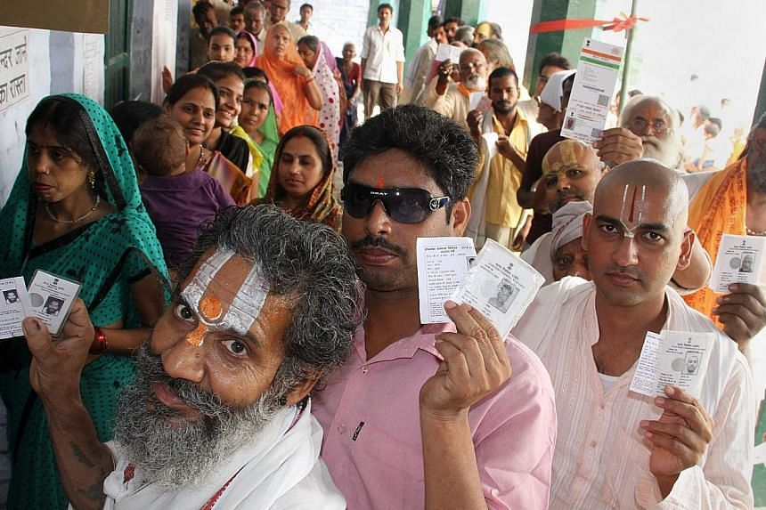 Indian voters display their identification cards as they wait to cast their ballots at a polling station in Ayodhya on May 7, 2014. Instead of throwing out the unique identification card Aadhaar, created by the previous government, the Modi regime wi