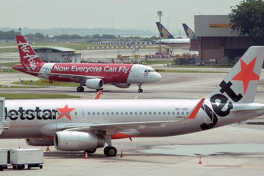 Aircraft of Australian low-cost carrier Jetstar Airways and Malaysian low-cost carrier AirAsia are seen at Changi International Airport in Singapore on May 8, 2014. Australian budget airline Jetstar apologised on Wednesday after a crew member to