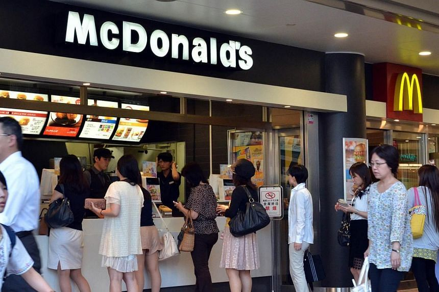 Customers order food at a McDonald's restaurant in Tokyo on July 25, 2014. -- PHOTO: AFP