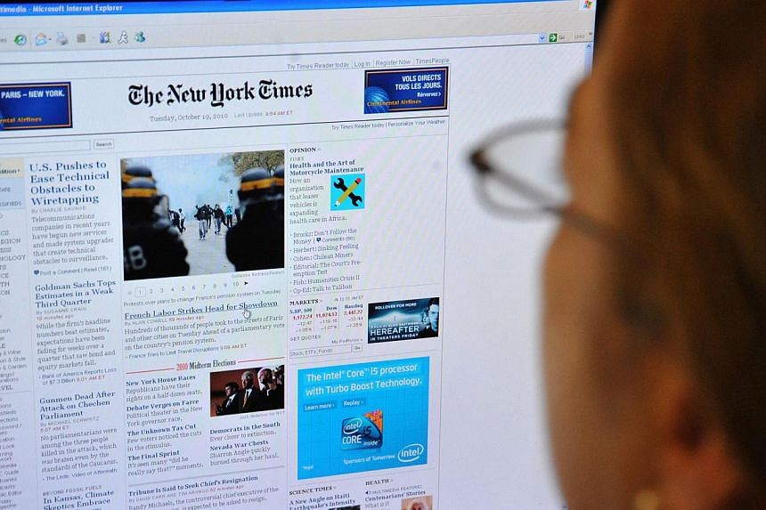 A woman reads the front page of the New York Times on the Internet on Oct 19, 2010 in Washington, DC. The New York Times Co on Tuesday, July 29, 2014, reported a sharp drop in profits as lower advertising revenues offset gains in digital subscription