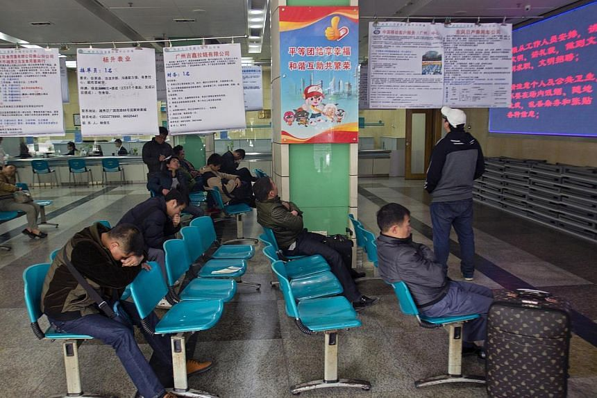 Job seekers wait next to recruitment advertisements at a labour market in Guangzhou, Guangdong province, on Feb 24, 2014.China plans to release figures for unemployment in its big cities in a timely manner, the cabinet said on Wednesday, a chan