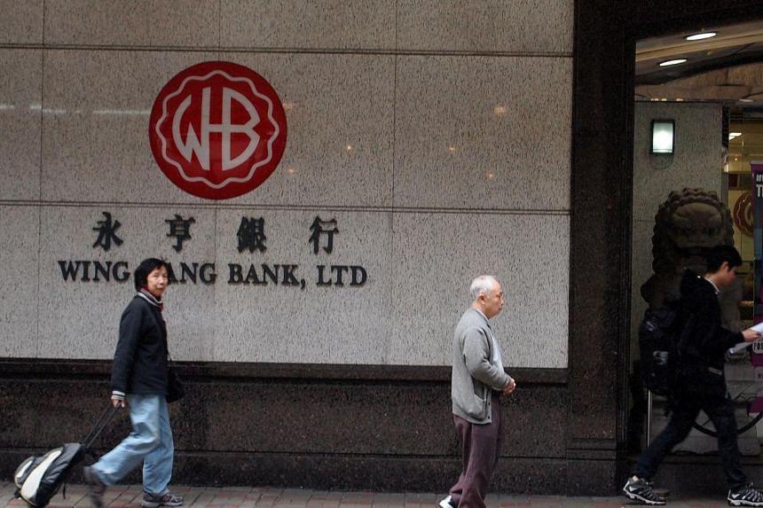 Passerbys walk past the main branch of the 77-year-old Wing Hang Bank at Sheung Wan, Hong Kong. -- PHOTO: ST FILE