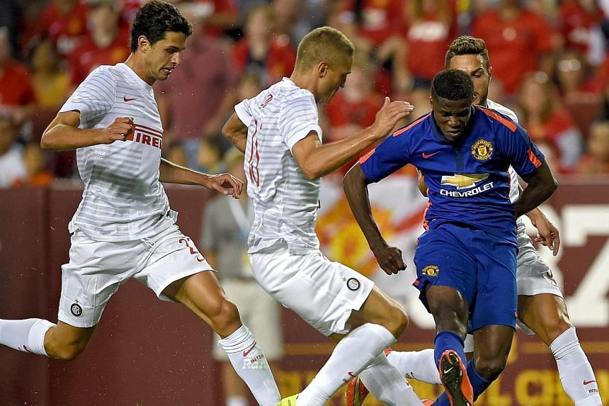 Manchester United'sWilfried Zaha (in blue) shoots as he is defended by Inter Milan players in the second half during their match in the International Champions Cup 2014 at FedExField on July 29, 2014, in Landover, Maryland.-- PHOTO: AFP