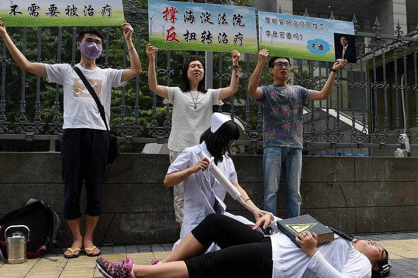 """Xiao Tie, executive director of the Beijing LGBT Centre, pretends to inject a patient with a mock syringe during a protest outside the Haidian District Court in Beijing on Thursday, July 31, 2014, as the court began hearing a landmark case on """"gay co"""