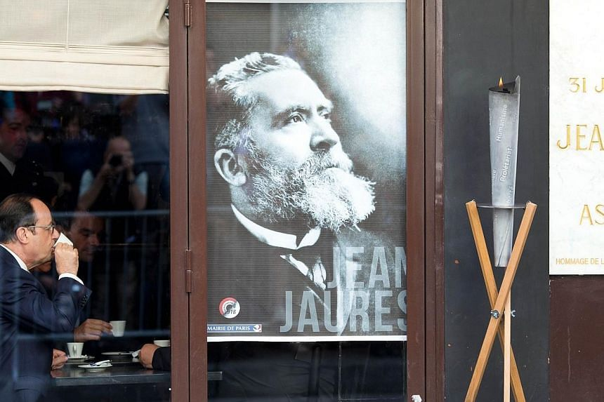 French President Francois Hollande drinks a cup of coffee by a portrait of Jean Jaures on July 31, 2014, inside the Cafe du Croissant after taking part to a commemoration ceremony at the place where French socialist leader and pacifist Jean Jaures wa