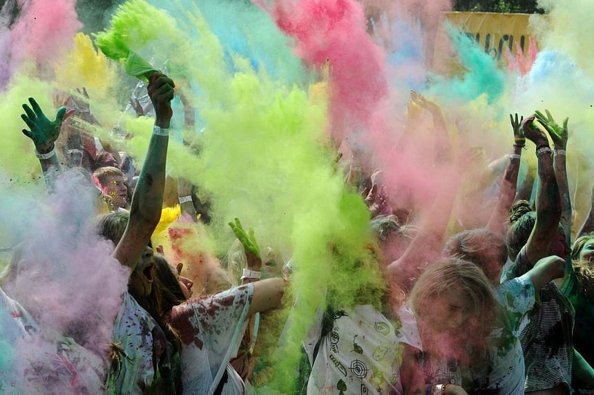 Youngsters throw colored powder at each other during the Festival of Colors in St. Petersburg on July 19, 2014.Russians are happier than ever despite being locked in a dramatic confrontation with the West over Ukraine that has seen their countr
