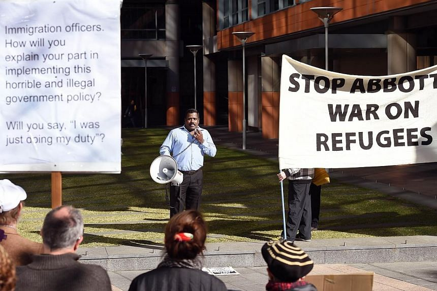 A man addresses the crowd at a rally protesting the Australian government's treatment of Sri Lankam asylum-seekers in Sydney on July 7, 2014.Australia's human rights commissioner said on Thursday, July 31, 2014, the government must come clean a