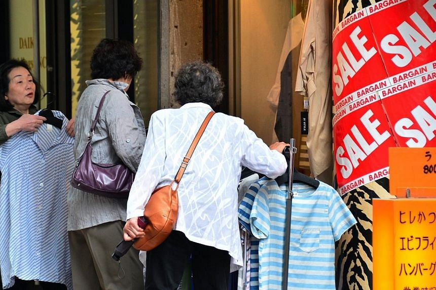 Customers browse shirts at an apparel shop in Tokyo on May 15, 2014.Japan must raise its sales tax again to conquer one of the world's heaviest public debt burdens, the International Monetary Fund (IMF) said on Thursday, July 31, 2014, as it ca
