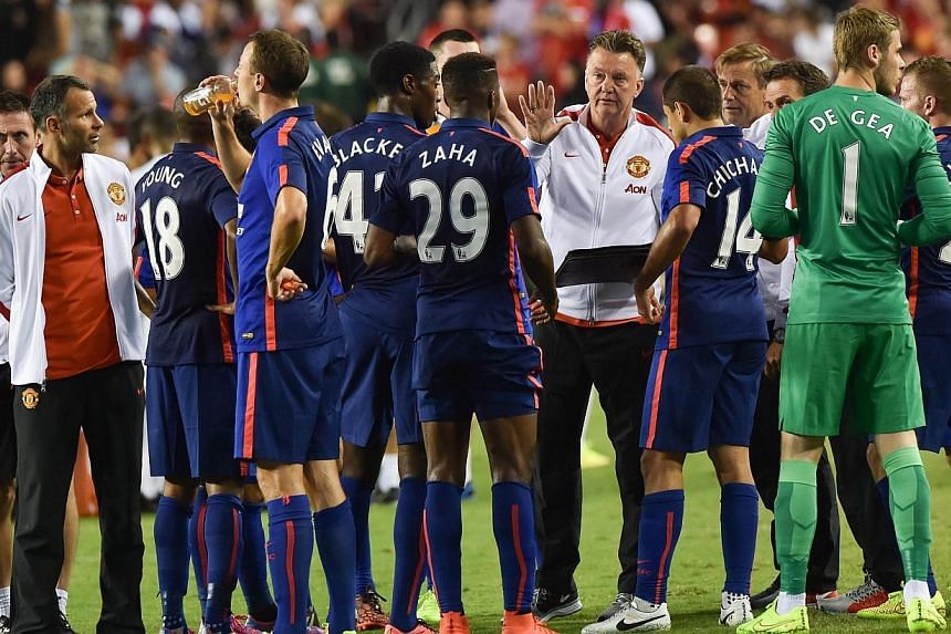 Manchester United's coach Louis van Gaal speaks to his players before a penalty shootout against Inter Milan during a Champions Cup match at FedEx Field in Landover, Maryland on July 29, 2014.Manchester United's owners on Thursday, July 31, 2