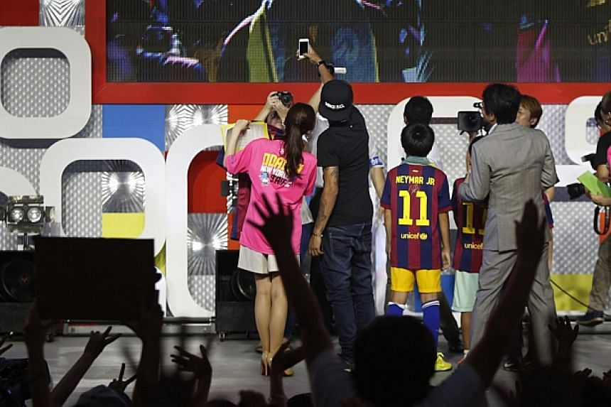 Brazilian soccer player and Barcelona forward Neymar takes pictures using his mobile phone during a fan event in Tokyo on July 31, 2014. -- PHOTO: REUTERS