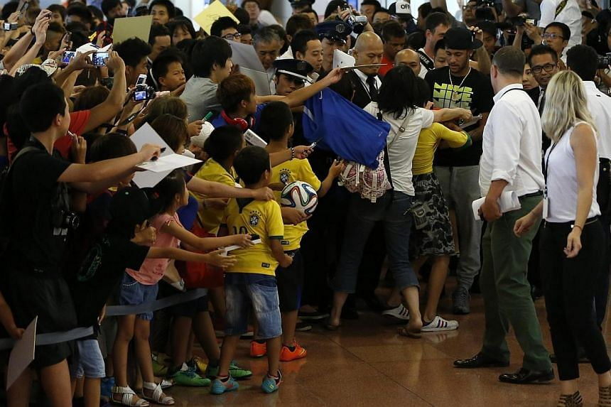 Brazilian soccer player and Barcelona forward Neymar (right) signs his autograph for fans upon his arrival at Tokyo's Haneda airport on July 31, 2014. -- PHOTO: REUTERS