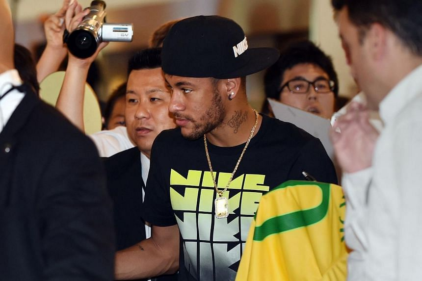 Brazilian football star Neymar (centre) is surrounded by fans upon his arrival at Haneda International Airport in Tokyo on July 31, 2014. -- PHOTO: AFP