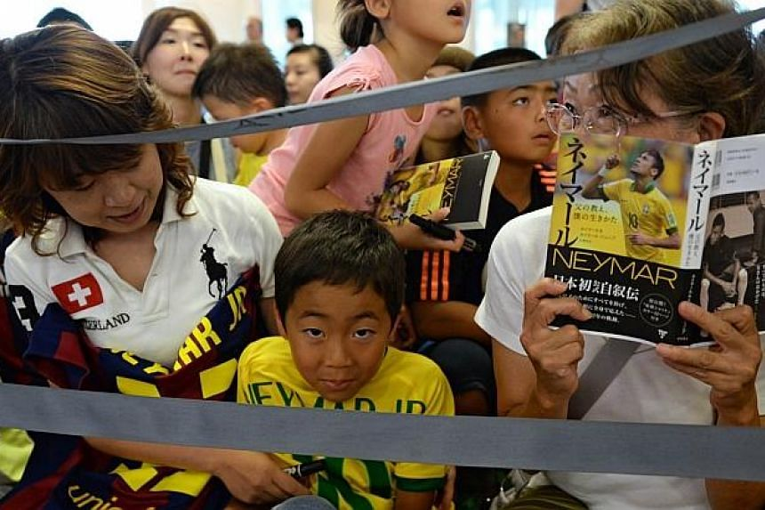Fans wait for Brazilian football star Neymar to arrive at the Haneda International Airport in Tokyo on July 31, 2014. -- PHOTO: AFP
