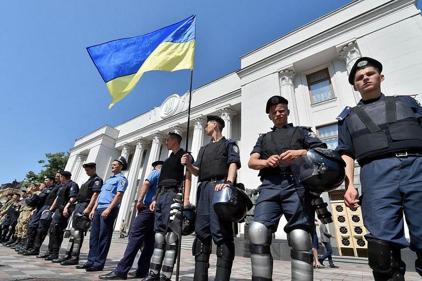 Policemen stand guard in front of the Ukrainian Parliament during a closed session in Kiev on July 31, 2014.Kiev on Thursday, July 31, 2014, announced a day-long halt to its deadly offensive to oust pro-Russian rebels in east Ukraine after figh