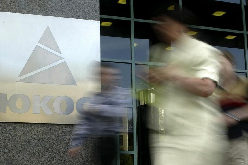 People walk by the Yukos oil company headquarters in Moscow on July 8, 2004.The European Court of Human Rights on Thursday, July 31, 2014, ordered Russia to pay former shareholders in defunct oil giant Yukos almost 1.9 billion euros (S$3.17 bil
