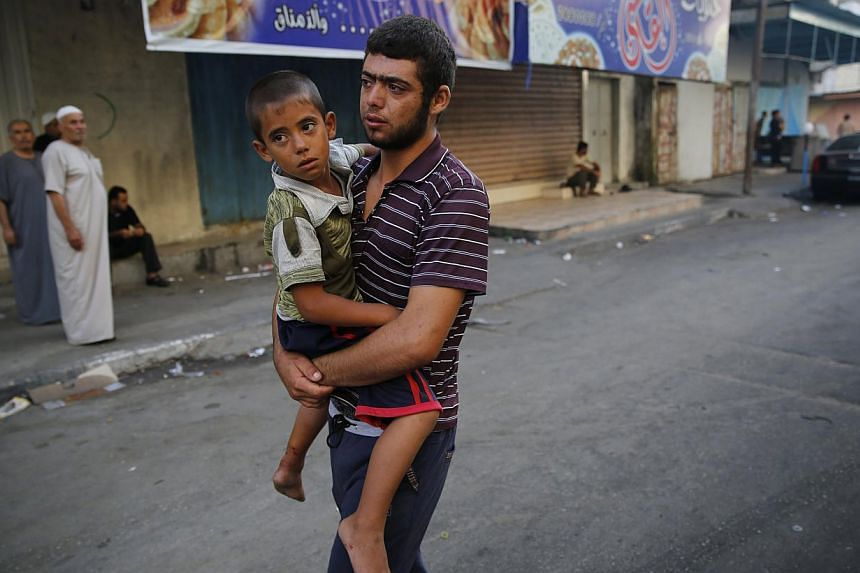 A Palestinian man carrying a child, who was injured by what medics said was Israeli shelling during an Israeli ground offensive, from a hospital in Beit Lahita in the northern Gaza Strip yesterday.