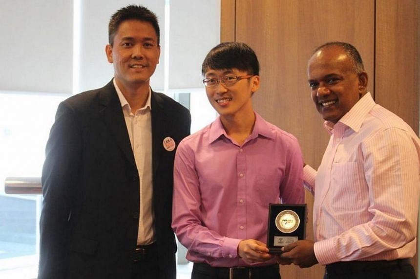The Bone Marrow Donor Programme's 100th donor Lim Yun Song (centre) receives a token of appreciation from Minister for Law and Foreign Affairs K Shanmugam (right), the programme's new patron, and the organisation's honorary secretary Martin Thoo. --