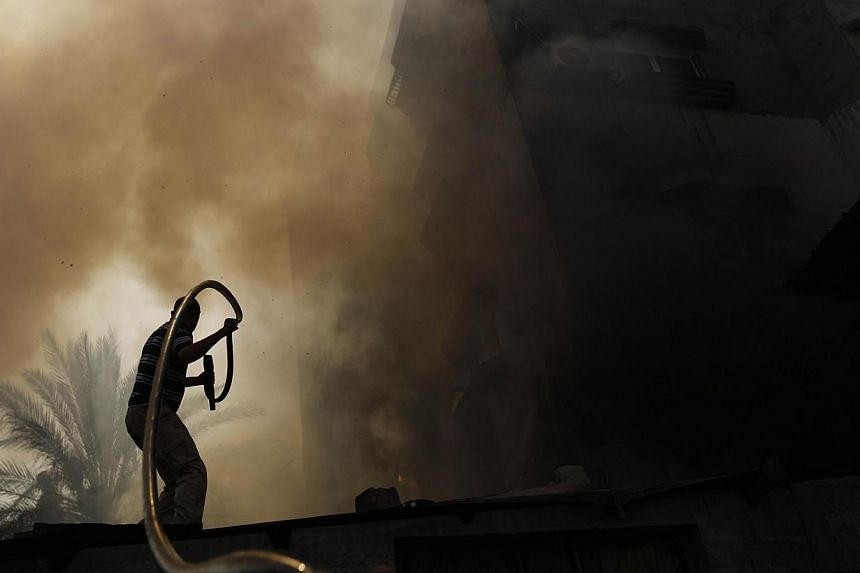 A Palestinian man battles a building on fire following several Israeli strikes on Gaza City on July 30, 2014.At least 17 people were killed in an Israeli strike on a packed Gaza market on Wednesday in a raid that came as Israel observed a four-