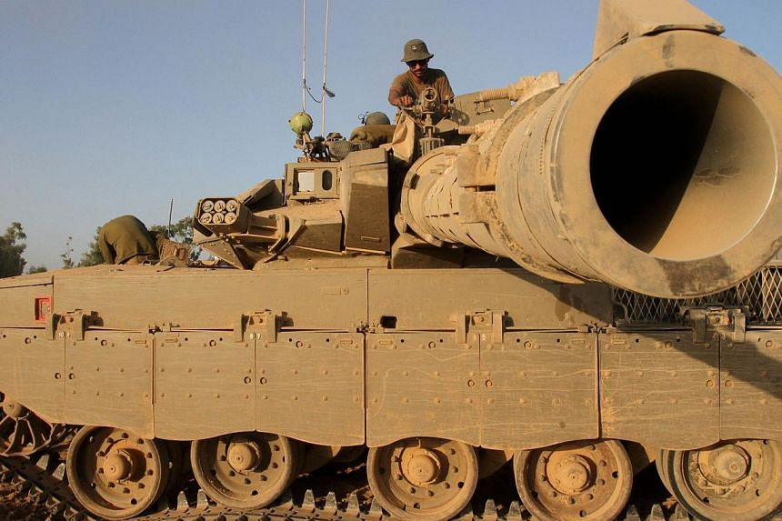 An Israeli soldier sits on top of a Merkava tank along the border between Israel and the Hamas-controlled Gaza Strip, on July 30, 2014, after returning from combat in the Palestinian enclave. -- PHOTO: AFP