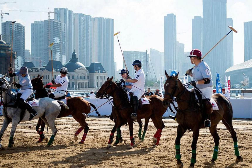 This photo taken on July 5, 2014 shows people playing polo on a field in the city of Dalian in north-east China's Liaoning province. A growing number of the country's wealthy elite are discovering the joys of the saddle and the whip. -- PHOTO: AFP