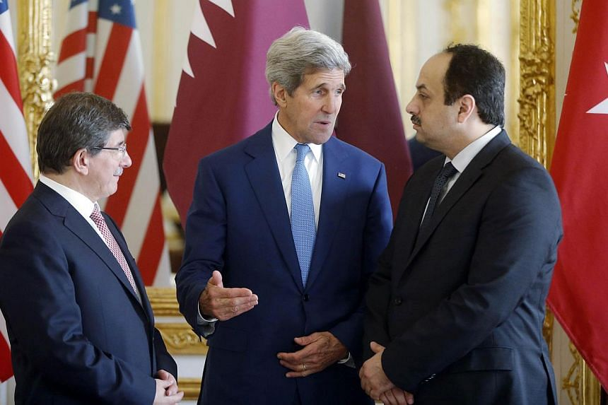 (From left) Turkish Foreign Minister Ahmet Davutoglu, US Secretary of State John Kerry and Qatari Foreign Minister Khaled al-Attiyah speak after their meeting regarding a cease-fire between Hamas and Israel in Gaza, at the foreign ministry in Paris,